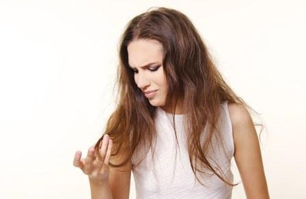 На фото женщина рассматривает свои волосы.