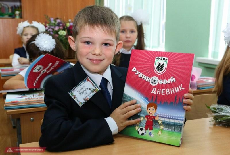 Школьный дневник в руках ребенка.