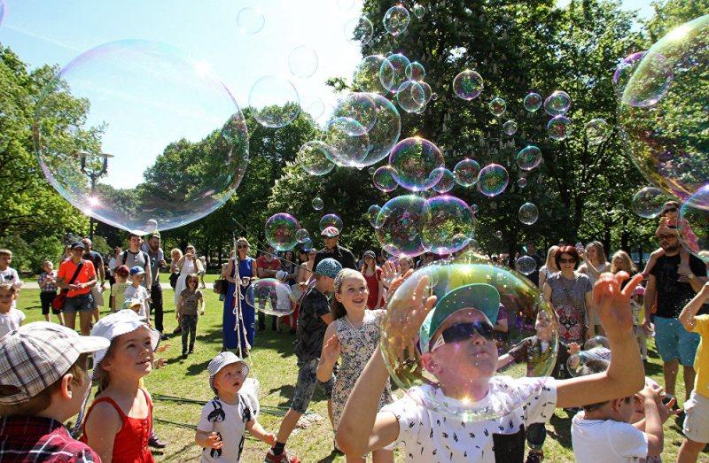 На фото группа детей запускает мыльные пузыри.
