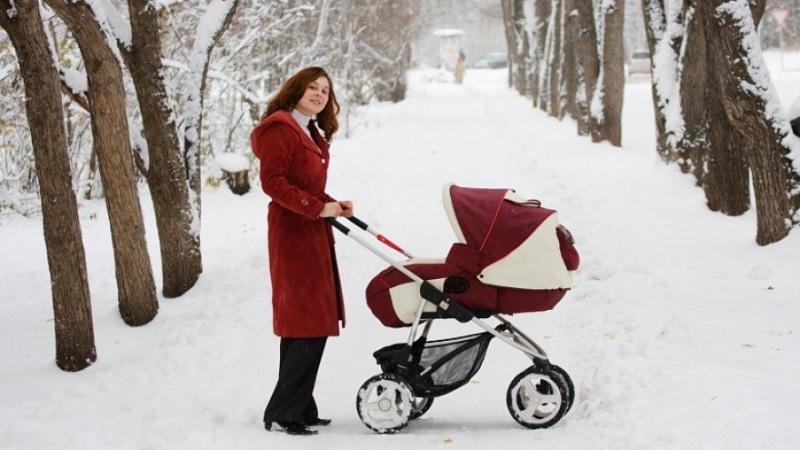 Новорожденный в коляске зимой.