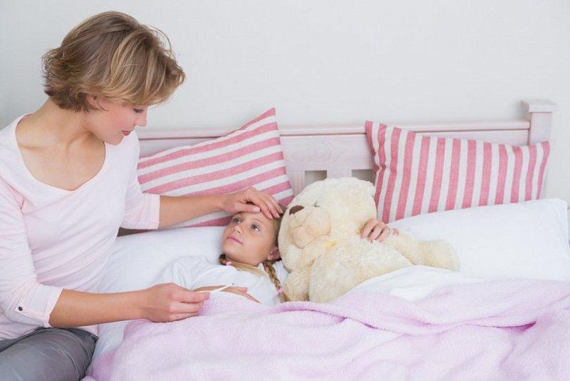 На фото ребенок в постели.