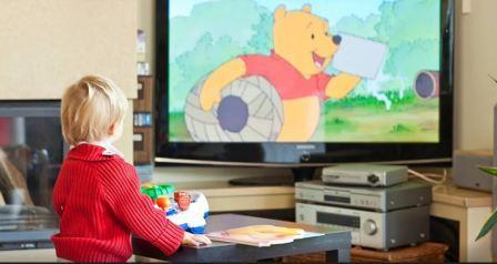 На фото ребенок смотрит мультфильм по телевизору