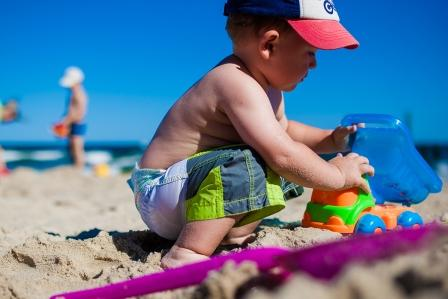На фото ребенок играет на пляже.