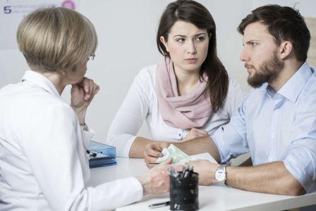 На фото мужчина и женщина на приеме у врача репродуктивной медицины.