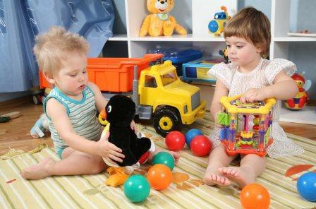 На фото маленькие дети с игрушками.