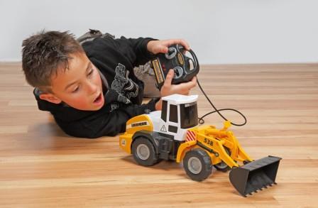 На фото мальчик играет с мини бульдозером