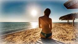 Девушка загорает утром на пляже