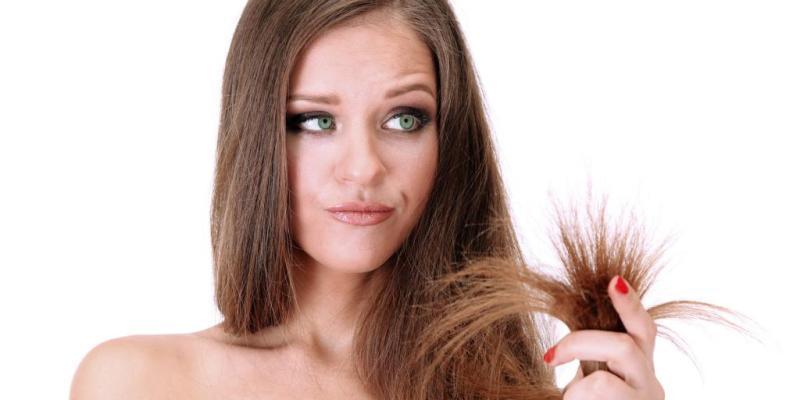 На фото девушка рассматривает свои секущиеся волосы.