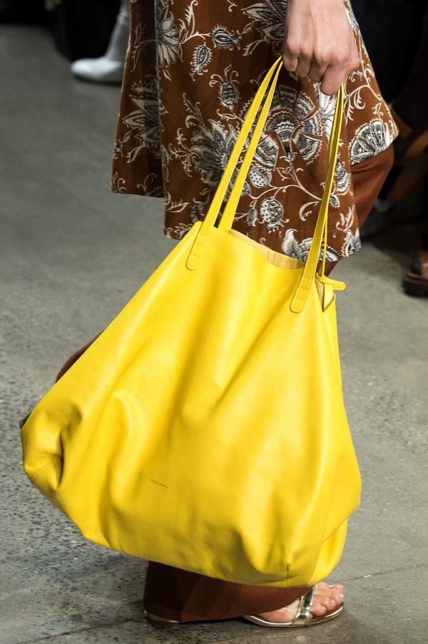 На фото большая желтая сумка - аксессуар входит в моду в текущем сезоне.