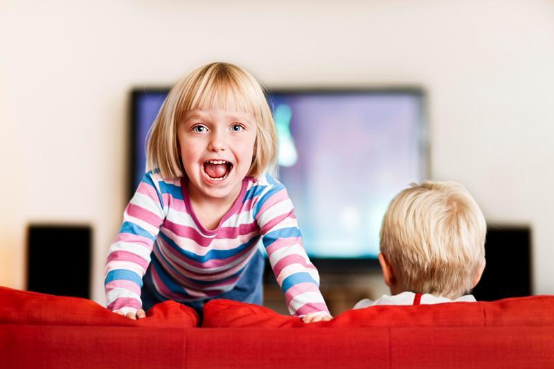 На фото ребенок отвернулся от телевизора.