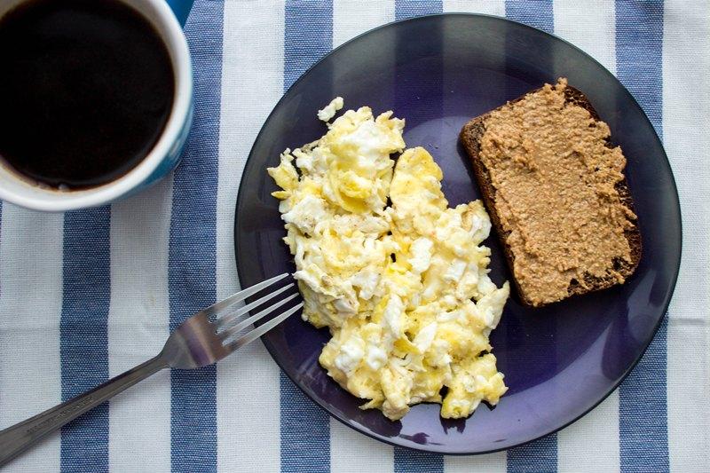 На фото показан завтрак, составленный из яичницы и черного хлеба