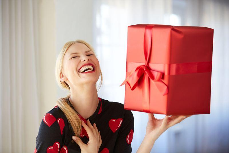 На фото счастливая женщина с подарком