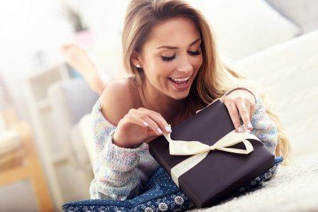 На фото девушка открывает подарок